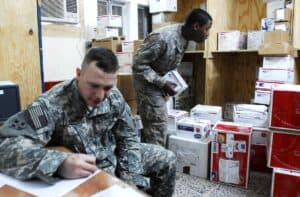 Two soldiers process mail in a US Army Forward Operating Base Mailroom
